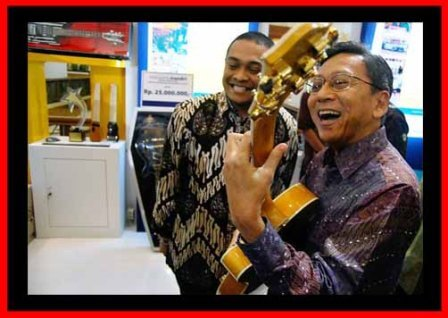 Pak Budiono memakai gitar stranough